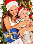 Weihnachtsfamilie mit Geschenkbox unterm Weihnachtsbaum.