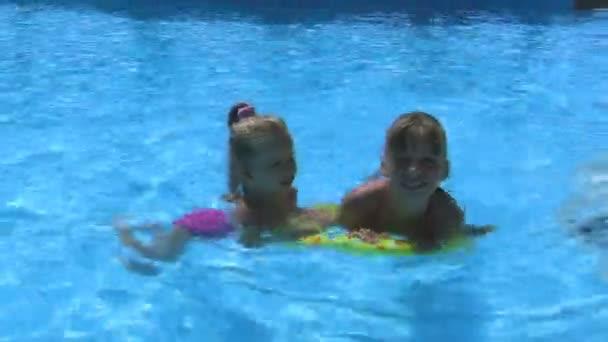 Kinder tragen Sonnenbrillen schwimmt auf aufblasbaren Ring sind im Pool schwimmen.