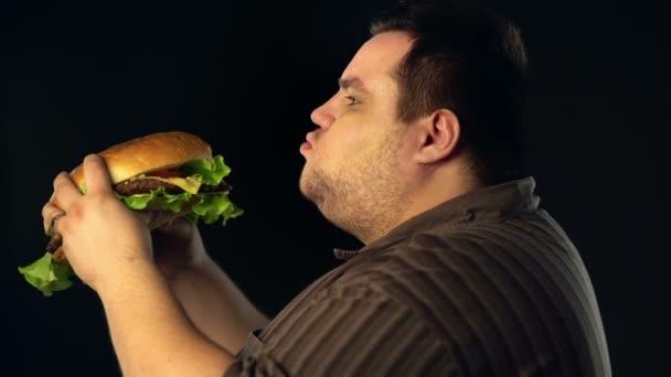 dicker Mann, der Hamburger Fast Food isst. Frühstück für Übergewichtige.