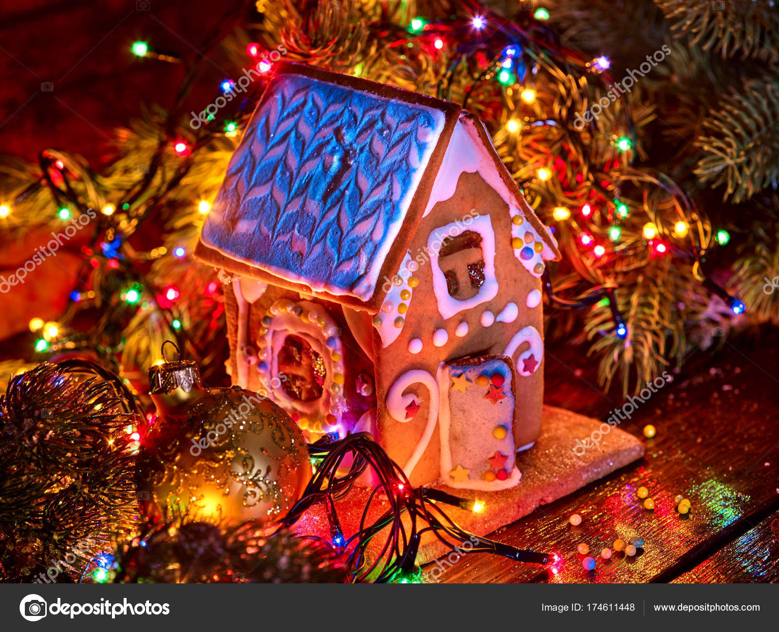 Gingerbread houses with christmas lights string on wooden table