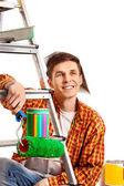 Fotografie Repair home man holding paint roller for wallpaper.