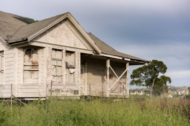 Abandoned single family home with wooden siding as fixer upper property
