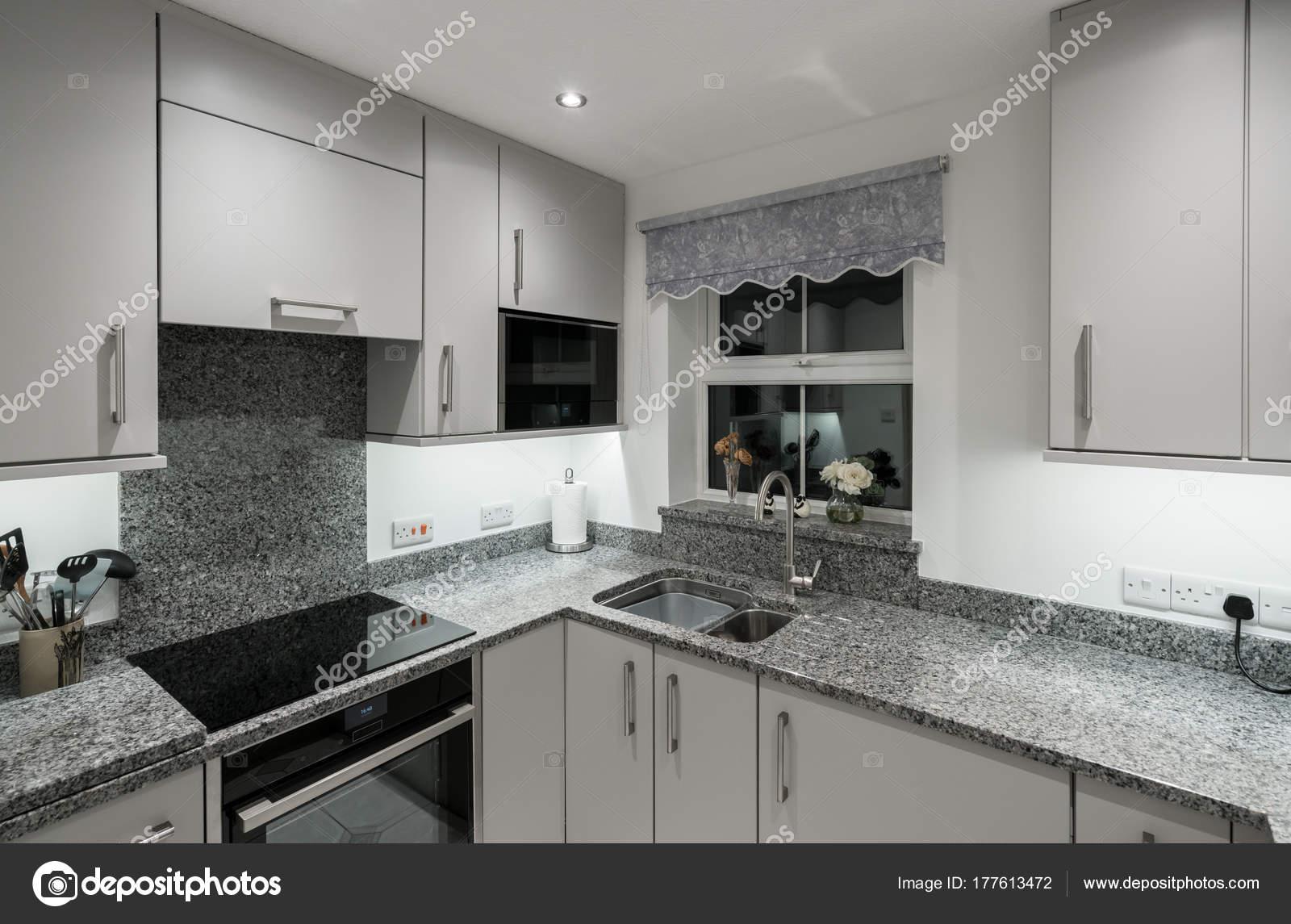 Kleine moderne keuken in appartement met granieten werkblad