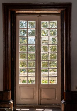 Old wooden glazed doors leading to ornate garden in old mansion