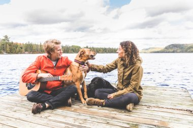 Happy couple playing with dog on a dock