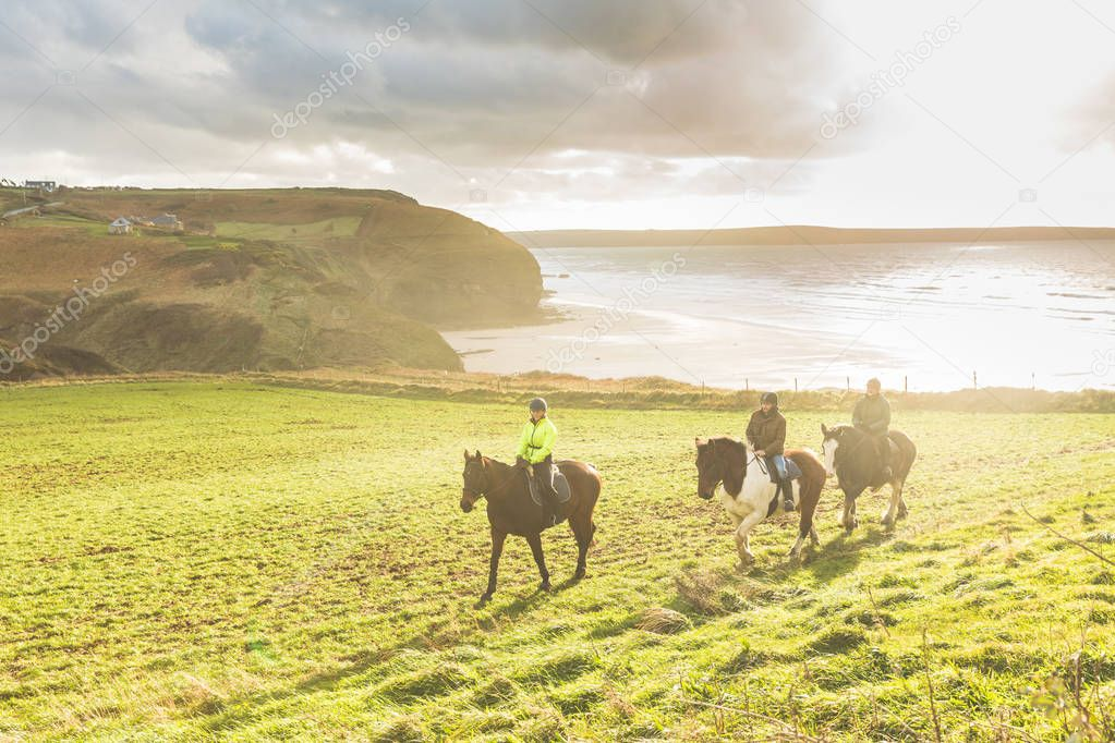 People riding horses in the countryside