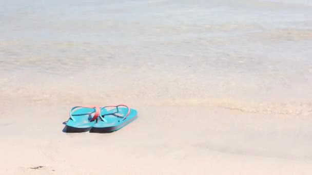 Flip flops on the beach with waves coming