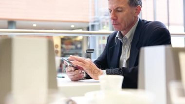 Businessman typing on the smart phone in a cafe