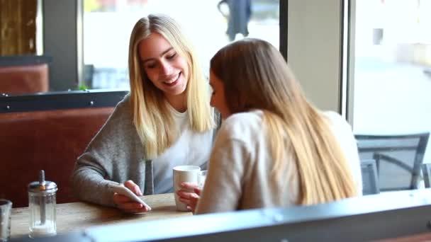 Dvě krásné dívky v kavárně pomocí smartphonu