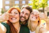 Amici che hanno divertimento insieme e prendendo un selfie