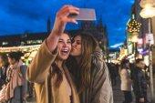 Fotografie Glückliche Mädchen, die eine Selfie zusammen zu Weihnachten Markt München