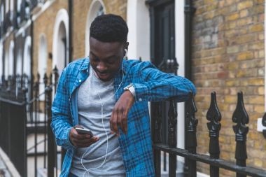 Black man listening music with phone in London