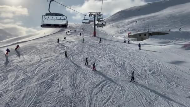 Lidé lyžují na zasněženém svahu v lyžařském středisku v horách