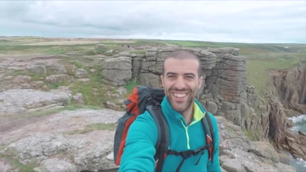 Man hiking and taking a selfie on top of cliffs