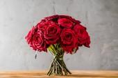 Fotografie Rudá růže na dřevěný stůl, zblízka