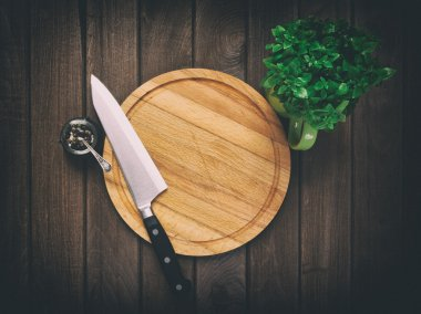 Chopping board on dark wooden background