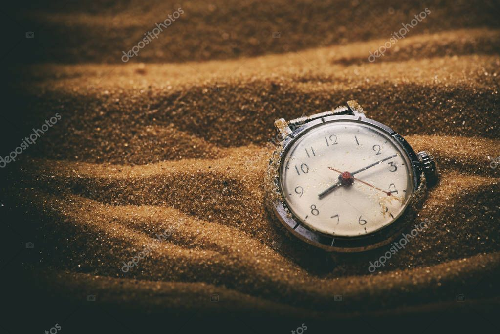 old retro watch on sand