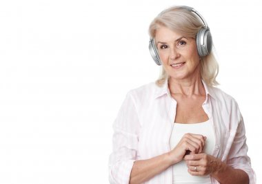 Portrait of a happy senior woman is listening to music with headphones. Isolated on white