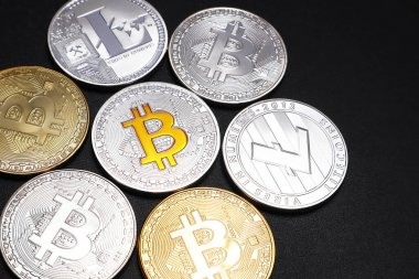 Coins of Bitcoin and Litecoin on a black textured background