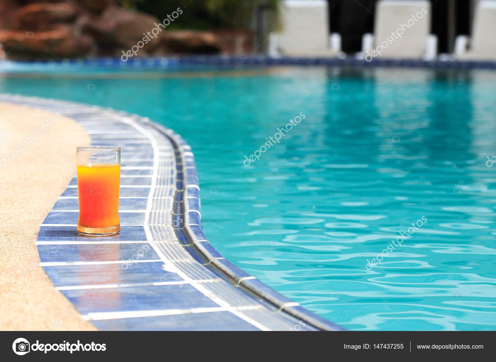 e23d8445223885 Close-up van jus d'orange glas staande op rand van zwembad — Foto van ...