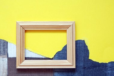 Blank wooden picture frame on abstract color background