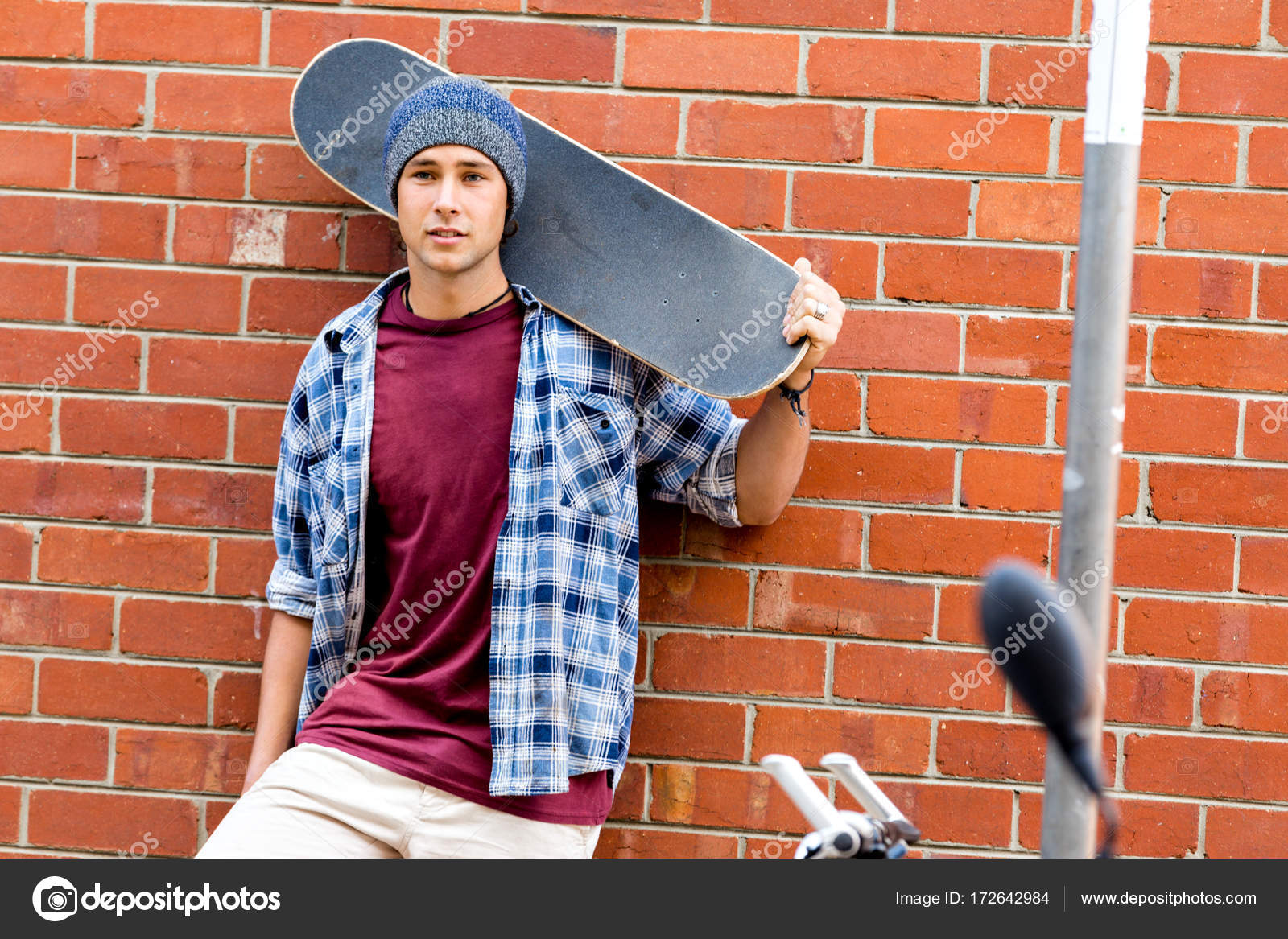 Teenage boy with skateboard standing next to the wall — Stock Photo