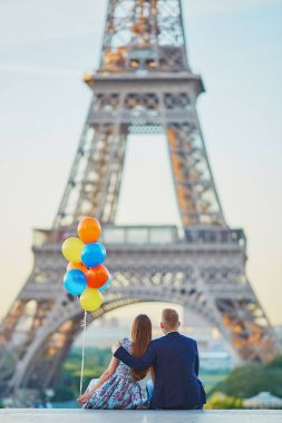 Couple with colorful balloons looking at the Eiffel tower
