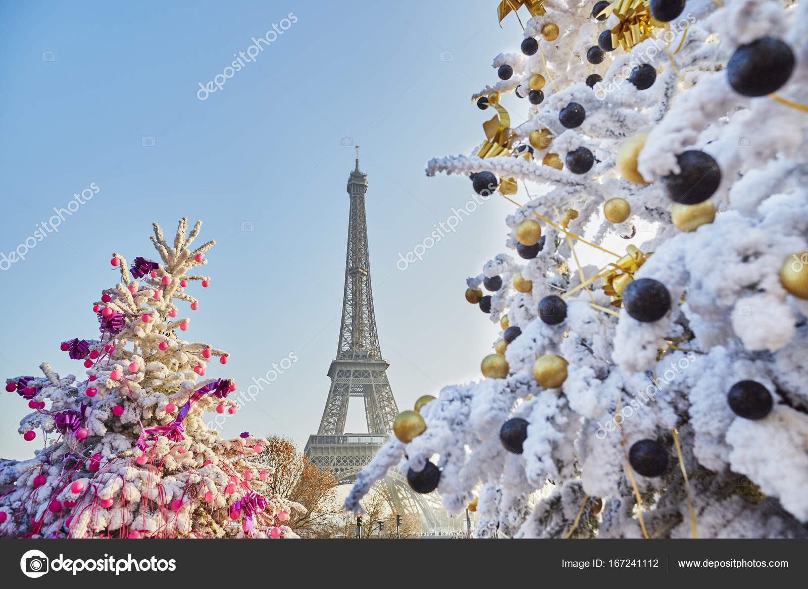 decorated christmas trees covered with snow near the eiffel tower in paris france photo by encrier