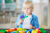 Fotografie Little boy playing with colorful plastic construction blocks