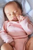 Novorozenec holčička klidně spí v postýlce
