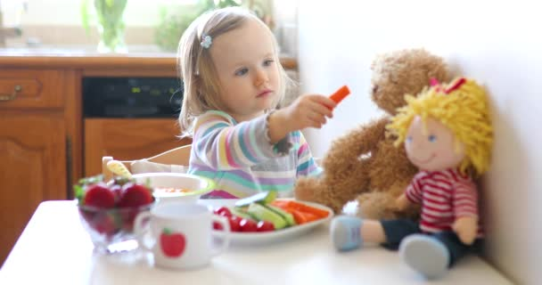Adorable toddler girl eating fresh fruits and vegetables for lunch. Child feeding doll and teddy bear in the kitchen. Delicious healthy food for kids