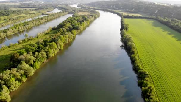 Scenic aerial view of the Seine river with boats and cargo barges and green fields in French countryside. Val dOise department, Ile-de-France, Northern France