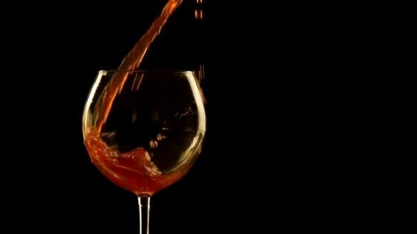 Dieses Video zeigt eine anonyme Hand, die schlampig und chaotisch Rotwein in ein Glas mit schwarzem Hintergrund gießt.