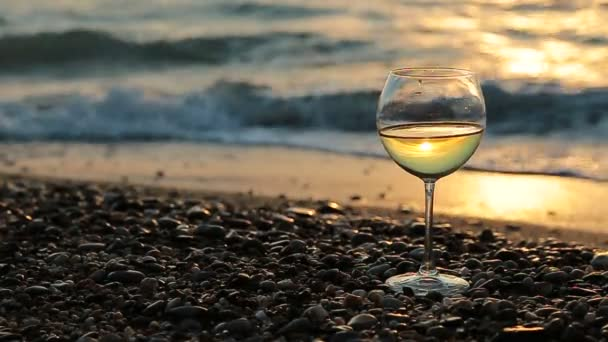 Glass of white wine on the beach at sunset. Sea waves