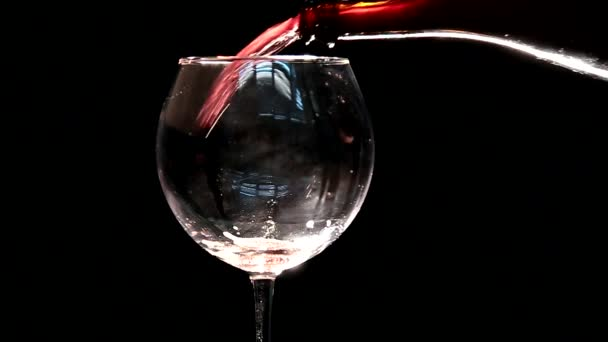 This video shows an anonymous hand making a sloppy and messy pour of red wine into a glass with a black background.