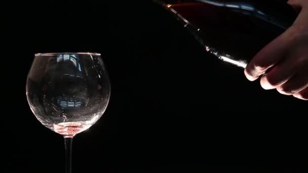 Ez a videó azt mutatja, egy névtelen kezét, hogy hanyag és piszkos öntsük a vörösbor egy pohár fekete háttér.