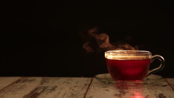 Pára z džbánu s teplými nápoji. Z džbánu s horkým nápojem se zvedá pramínek bílé páry. Podsvícení osvětluje béžový pohár na černém pozadí. Střelba rychlostí 240fps