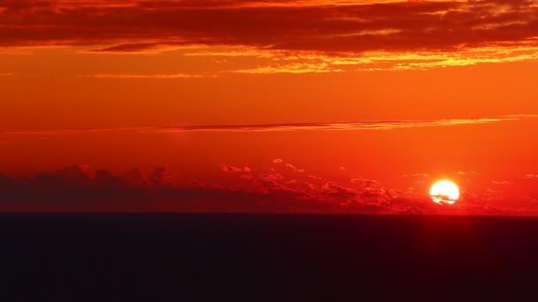 Západ slunce nad mořem. Slunce a oranžová obloha se odrážejí v příboji. Pomalý pohyb. 4k, UHD