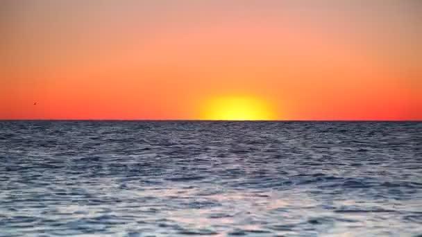 Sonnenuntergang über dem Meer. Sonne und orangefarbener Himmel spiegeln sich in der Brandung. Zeitlupenaufnahme. 4k, uhd