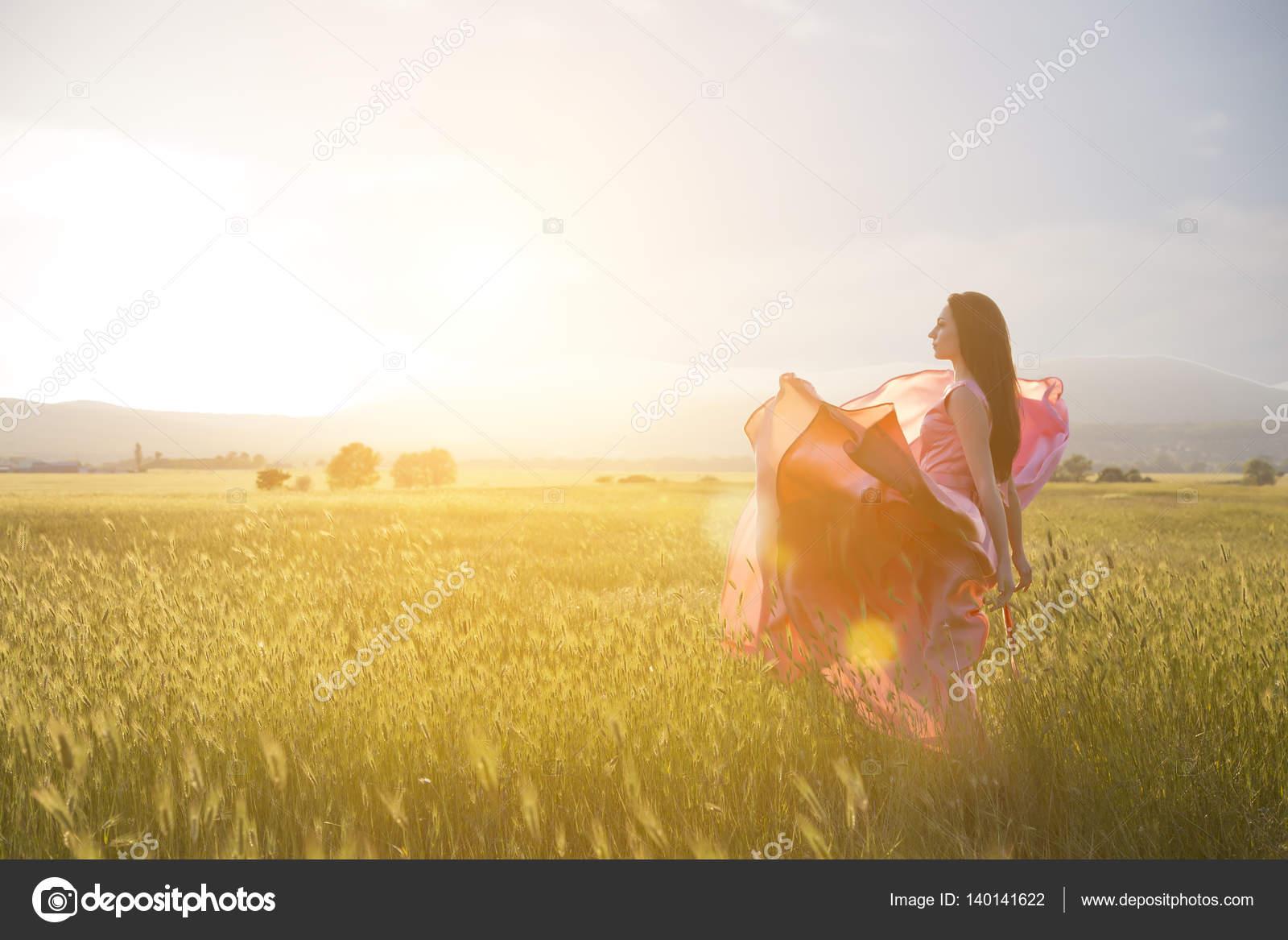 Giovane donna in piedi su un campo di grano con l 39 alba for Piani di studio 300 piedi quadrati