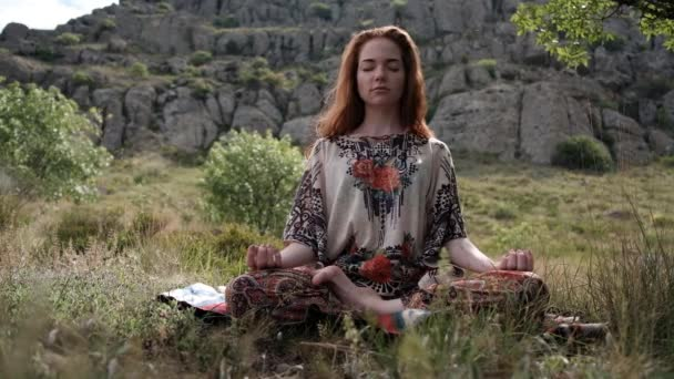 Beautiful and healthy ginger woman breathing gently and sits in pose of lotus