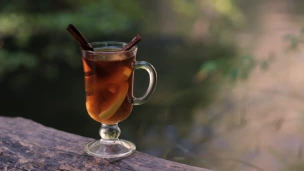sklenice čaje stojí na přírodě u řeky