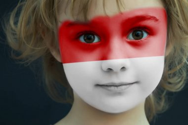 Child with a painted flag of Indonesia