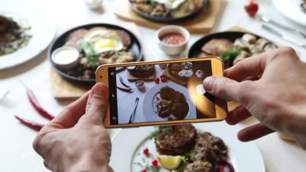 Ruce s fotografii různé pokrmy s smartphone