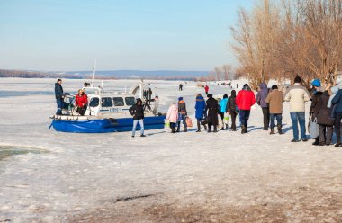 Embarkation people on the passenger hovercraft at the ice of the