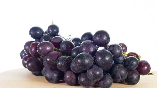 Black grapes rotates, white background, 4k stop motion