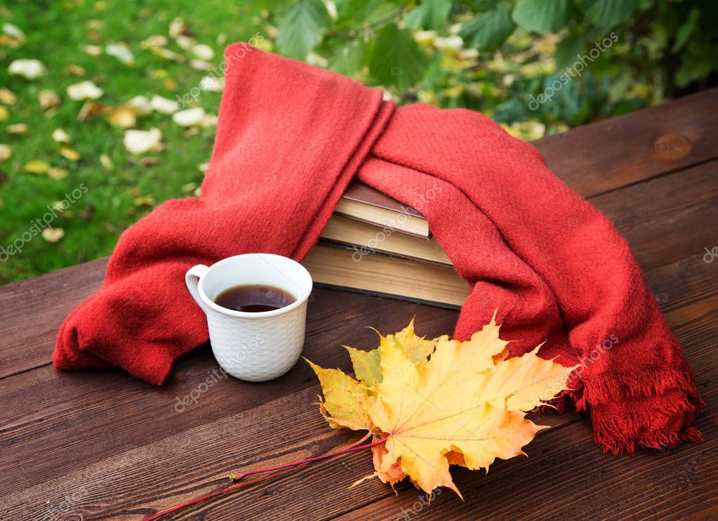 cup of tea on the table with a scarf and a pile of books