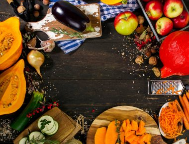 Autumn vegetables and fruits on a dark wooden board.