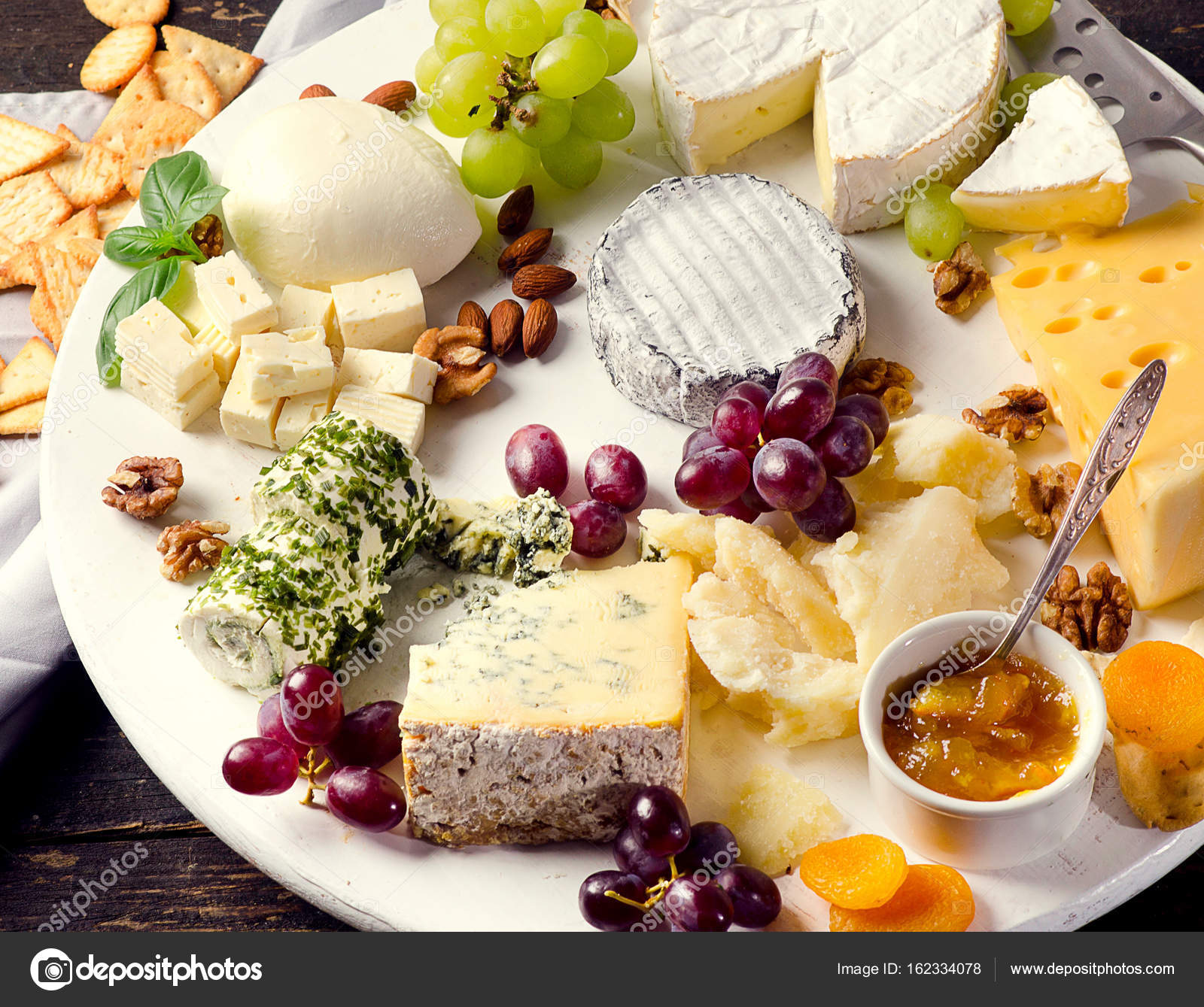 Cheese plates served with grapes jam and nuts on a wooden board. Top view \u2014 Photo by bit245 & Cheese plates served with grapes jam and nuts \u2014 Stock Photo ...
