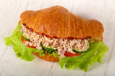 Croissant with minced meat over wooden background